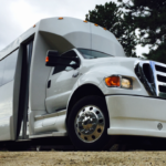 White shuttle bus by sunset luxury limousines
